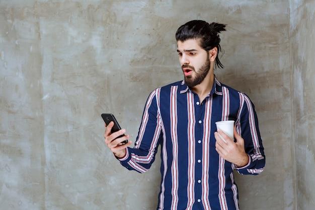 Мужчина в полосатой рубашке держит чашку с водой и играет со своим телефоном