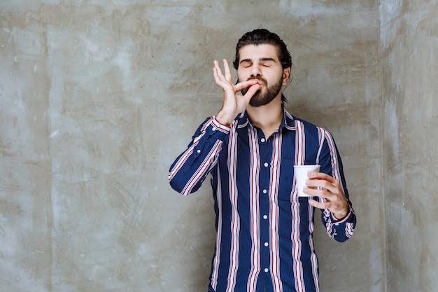 白い使い捨ての飲み物を持って味を楽しんでいる縞模様のシャツの男