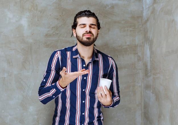 白い使い捨ての水カップを保持し、味の匂いを嗅ぐ縞模様のシャツの男