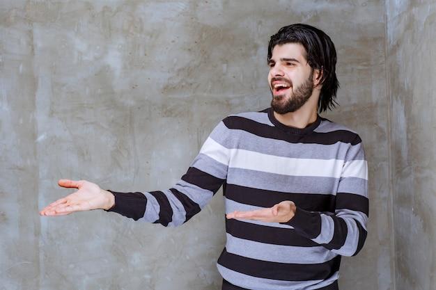 縞模様のシャツを着た男は驚いて混乱しているように見えます