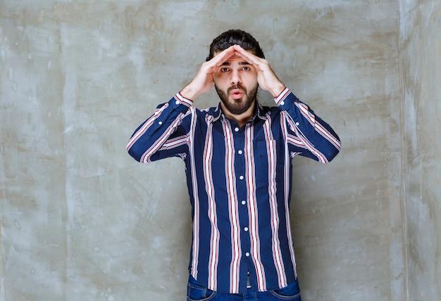 줄무늬 셔츠를 입은 남자가 이마에 손을 대고 관찰합니다.