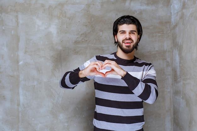Человек в полосатой рубашке показывает знак сердца