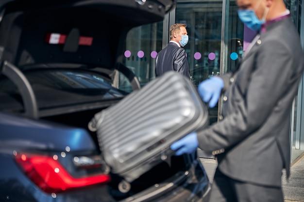 スーツと保護マスクの男は、飛行後にビジネスマンに会い、彼の荷物の世話をしています
