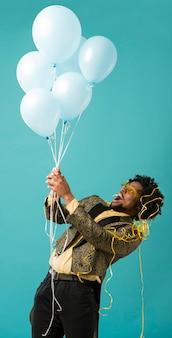 風船の肖像画とパーティーでスーツとサングラスの男