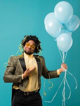 Человек в костюме и солнцезащитных очках на вечеринке с портретом воздушных шаров