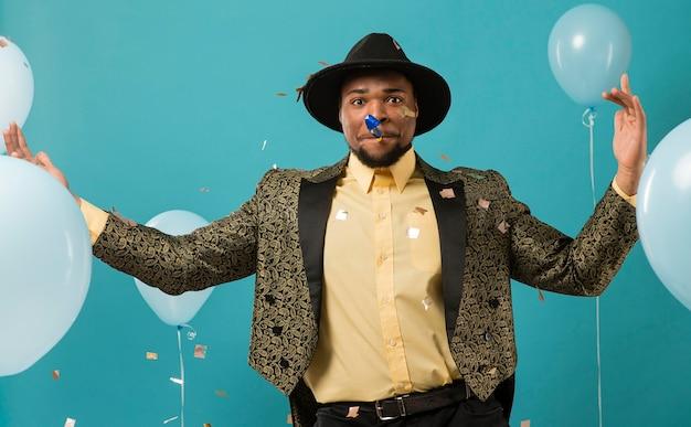 風船とパーティーでスーツとサングラスの男