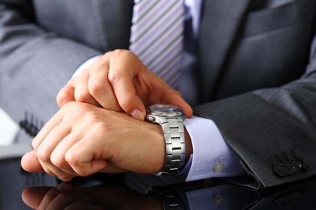 スーツとネクタイの男は銀の腕時計で時間をチェック
