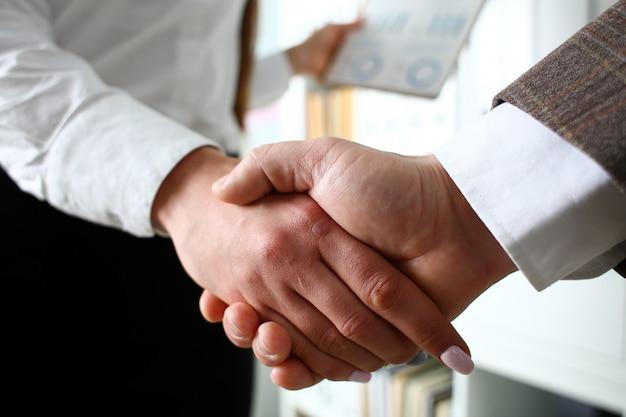 スーツとネクタイの男はオフィスでこんにちはとして手を与える