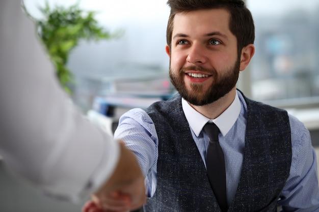 양복과 넥타이를 입은 남자가 사무실에서 인사합니다.