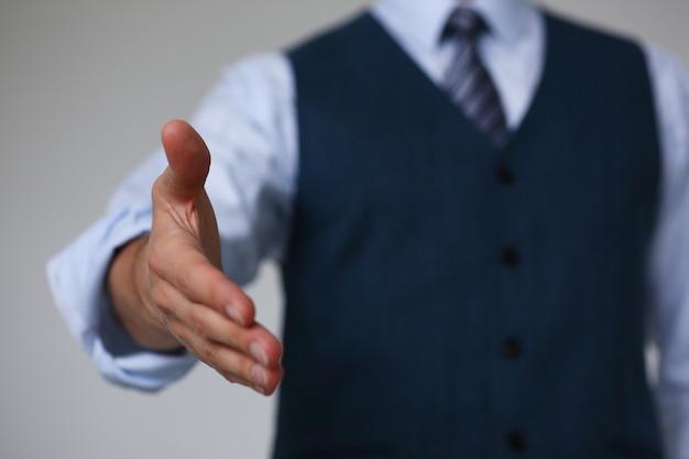 スーツとネクタイの男がオフィスでこんにちはとして手を差し伸べる