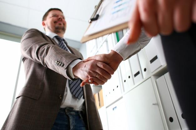 Человек в костюме и галстуке протянуть руку как привет в офисе