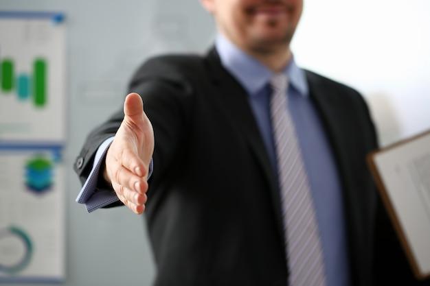 Человек в костюме и галстуке протянуть руку как привет