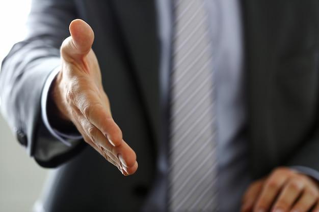 Человек в костюме и галстуке протягивает руку в офисе