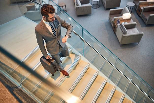 Мужчина в костюме и галстуке спускается по лестнице