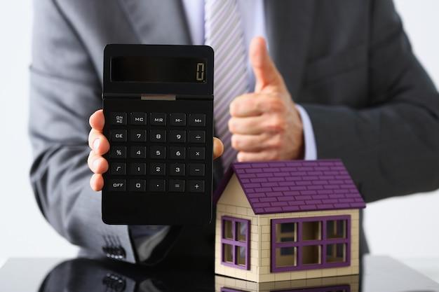 Мужчина в костюме и галстуке держит в руках калькулятор