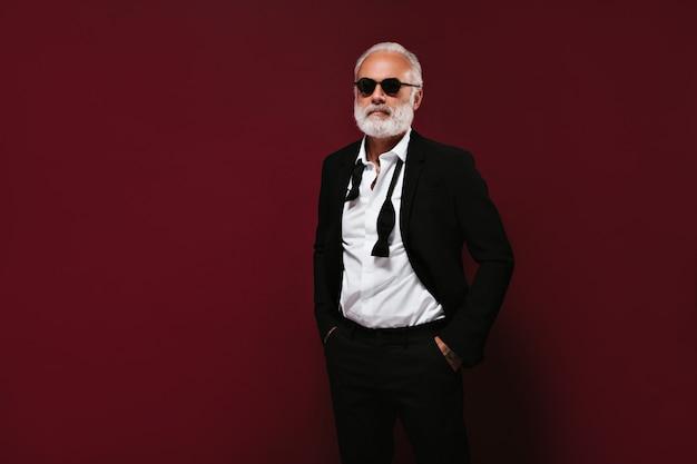 양복과 흰 셔츠를 입은 남자가 선글라스를 착용