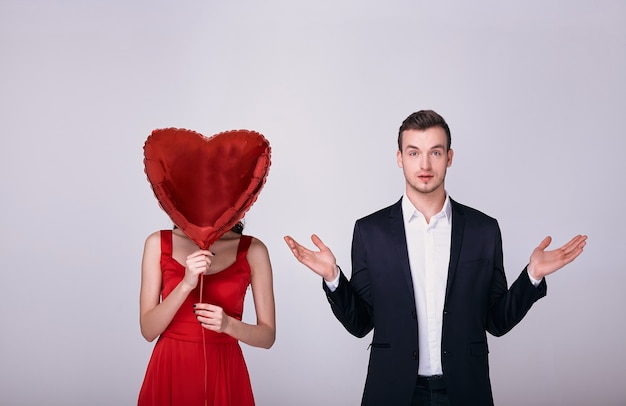 スーツを着た男性と赤いドレスの女性は、白い背景の上の彼女の顔に赤いハート型の風船を保持します。