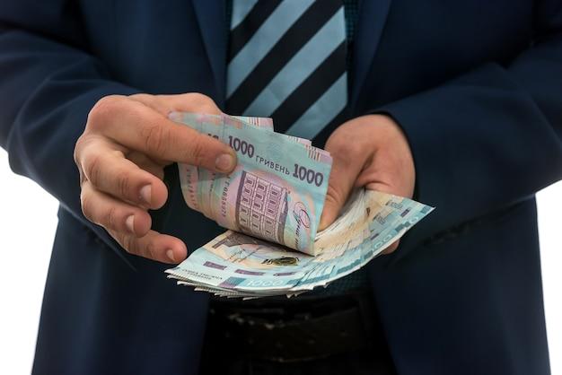 スーツを着た男は利益を数えます。男性の手はグリブナを変換します。 1000枚の新しい紙幣、ウクライナのお金