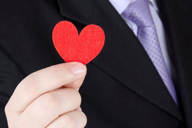 スーツを着た男がバレンタインデーのデートでファブリックハートギフトを贈る