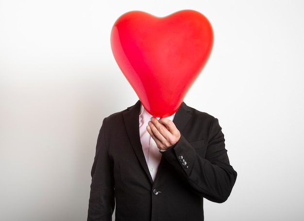 붉은 심장 모양의 풍선 뒤에 숨어 정장 남자. 사랑, 가족, 희망의 상징을 들고 남자.