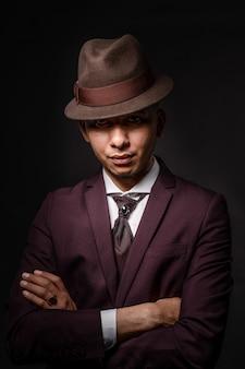 Человек в костюме, пряча лицо за шляпой, изолированной на темном фоне. секрет и концепция инкогнито