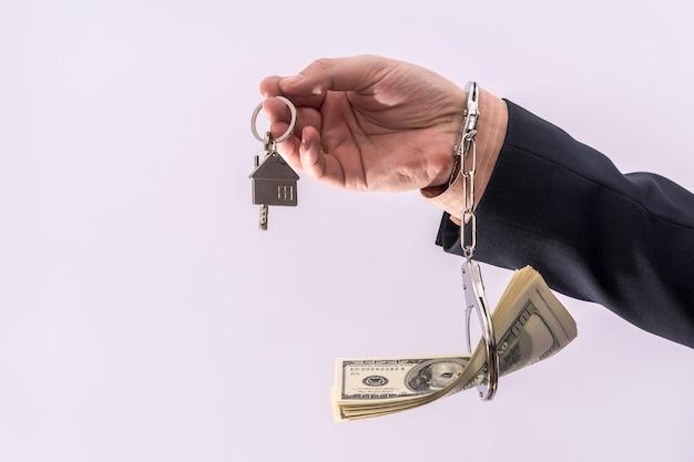 남자 정장 수갑에 달러와 집 열쇠를 잡아. 뇌물 부패 개념