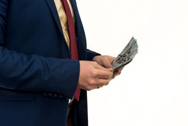 スーツを着た男は、白い壁に隔離された多くの私たちのお金のドルを保持します