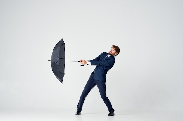 手に傘を持っているスーツの男エレガントなスタイルの天気の雨