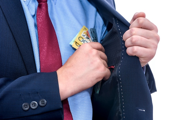 オーストラリアドル紙幣を保持しているスーツの男がクローズアップ