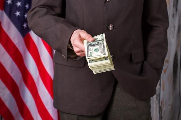 Человек в костюме, держащем доллары. флаг сша, человек и деньги. такое интересное предложение. мне нужны сильные друзья.
