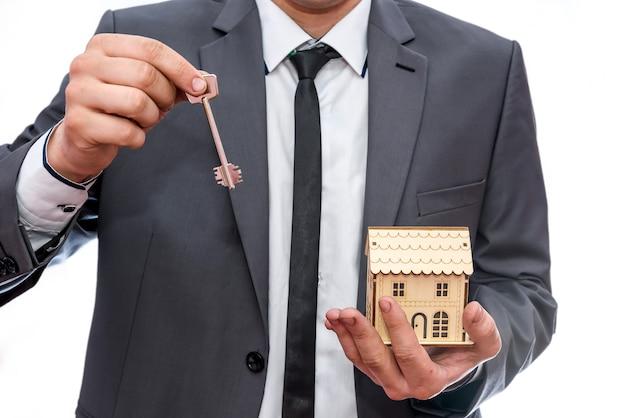 Мужчина в костюме держит модель дома и ключи