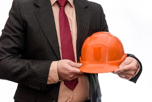 白で隔離オレンジ色のヘルメットを保持しているスーツの男