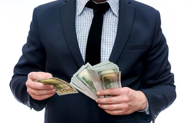 Мужчина в костюме держит кучу долларовых банкнот