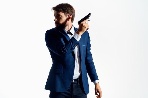 ピストル危険ギャング殺人の孤立した背景を保持しているスーツの男