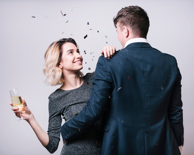 シャンパングラスを持つ女性を見るスーツの男