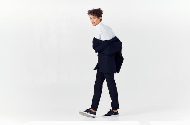 スーツのモダンなスタイルの男は、ファッションの明るい背景をポーズします