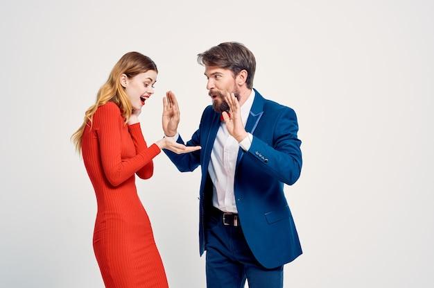 赤いドレスの感情のファッションで女性の隣にスーツを着た男