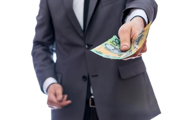 スーツを着た男がオーストラリアドル紙幣を提供