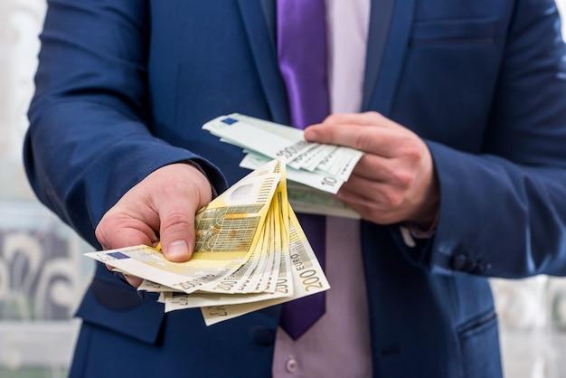 200ユーロ紙幣を提供するスーツの男