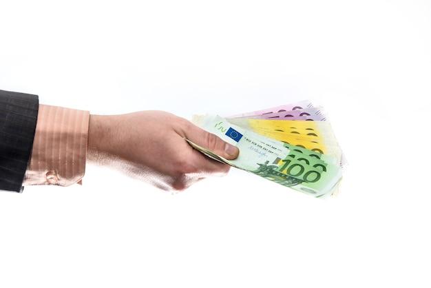 白で隔離されるユーロ紙幣を提供するスーツの男