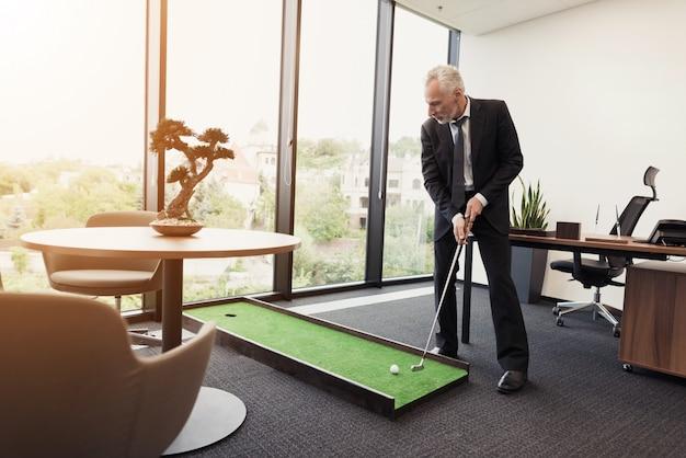 Человек в костюме играет в офисе в мини-гольф.