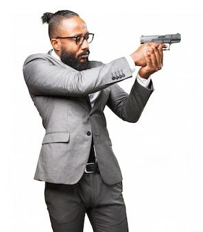 Человек в костюме, указывающий на пистолет