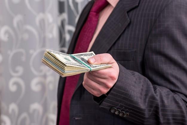 スーツの男はドルの束のクローズアップを提案します
