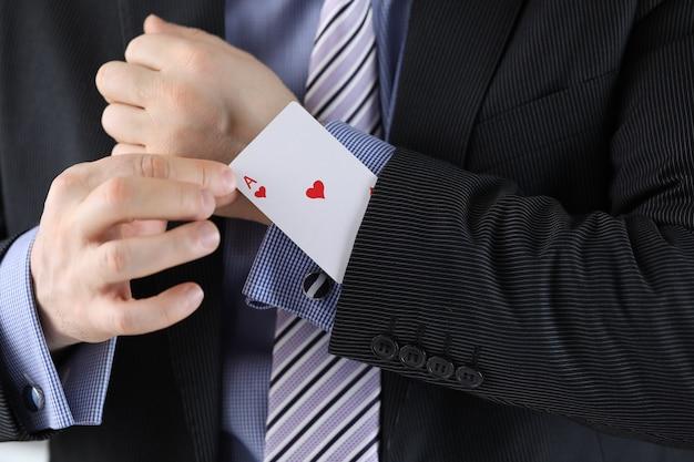 Мужчина в костюме засовывает в рукав пиджака туза чирв-карты