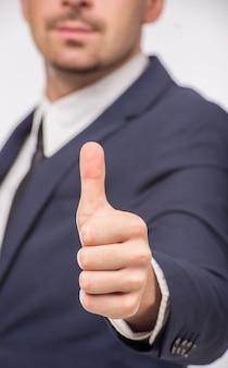 Человек в костюме показывая большой палец руки вверх на белой предпосылке.