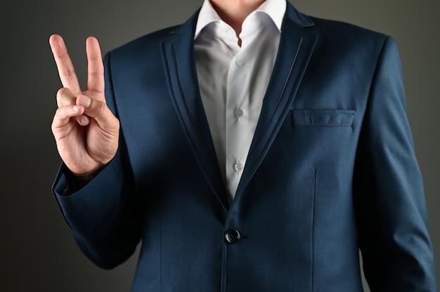 スーツを着た男は彼の手で平和のシンボルを示しています。高品質の写真