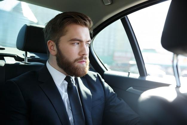 Человек в костюме сидит на заднем сиденье автомобиля
