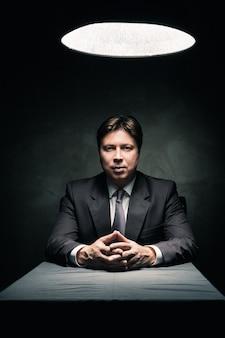 램프의 빛으로만 조명을 받고 카메라를 보고 있는 어두운 방에 앉아 있는 정장을 입은 남자