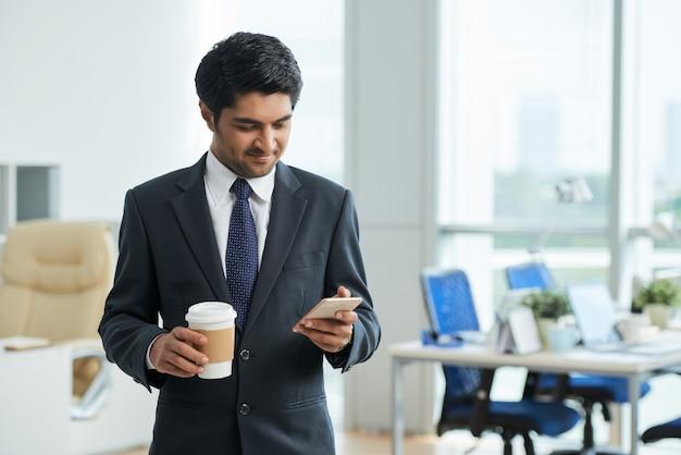 Человек в костюме стоял в офисе, держа кофе на вынос и с помощью смартфона