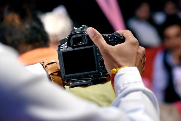 Человек в костюме фотографирует. концепция фотографии. фотограф держит камеру dsrl в руках с блеском белого размытия фона в помещении в студии или свадебном магазине с селективным фокусом